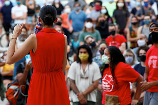 Masked protesters gather outside Denver City Hall after a hearing was cancelled due to social distancing concerns.