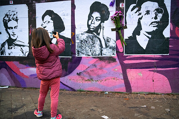 A girl photographs a feminist mural in Madrid, Spain on March 8, International Women's Day.