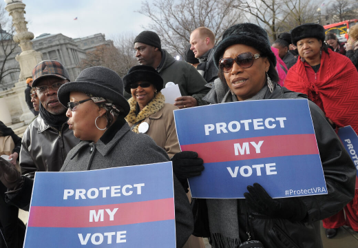 """Protestors holding signs that read """"Protect my vote""""."""