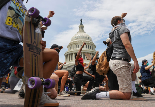 Protestors kneeing in front of the Capitol Building.