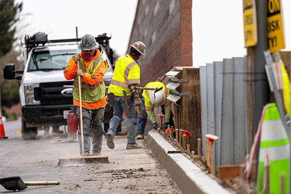 Contractors work on a road under repair along Highway 101.