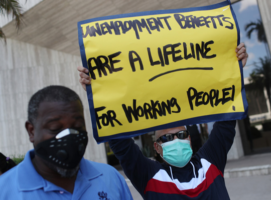 "Protestor wearing mask and holding sign that reads ""Unemployment benefits are a lifeline for working people."""