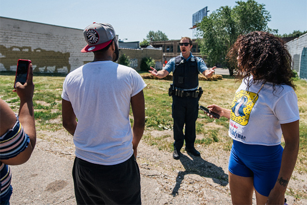 Local residents confront a Minneapolis police officer at a crime scene last summer.
